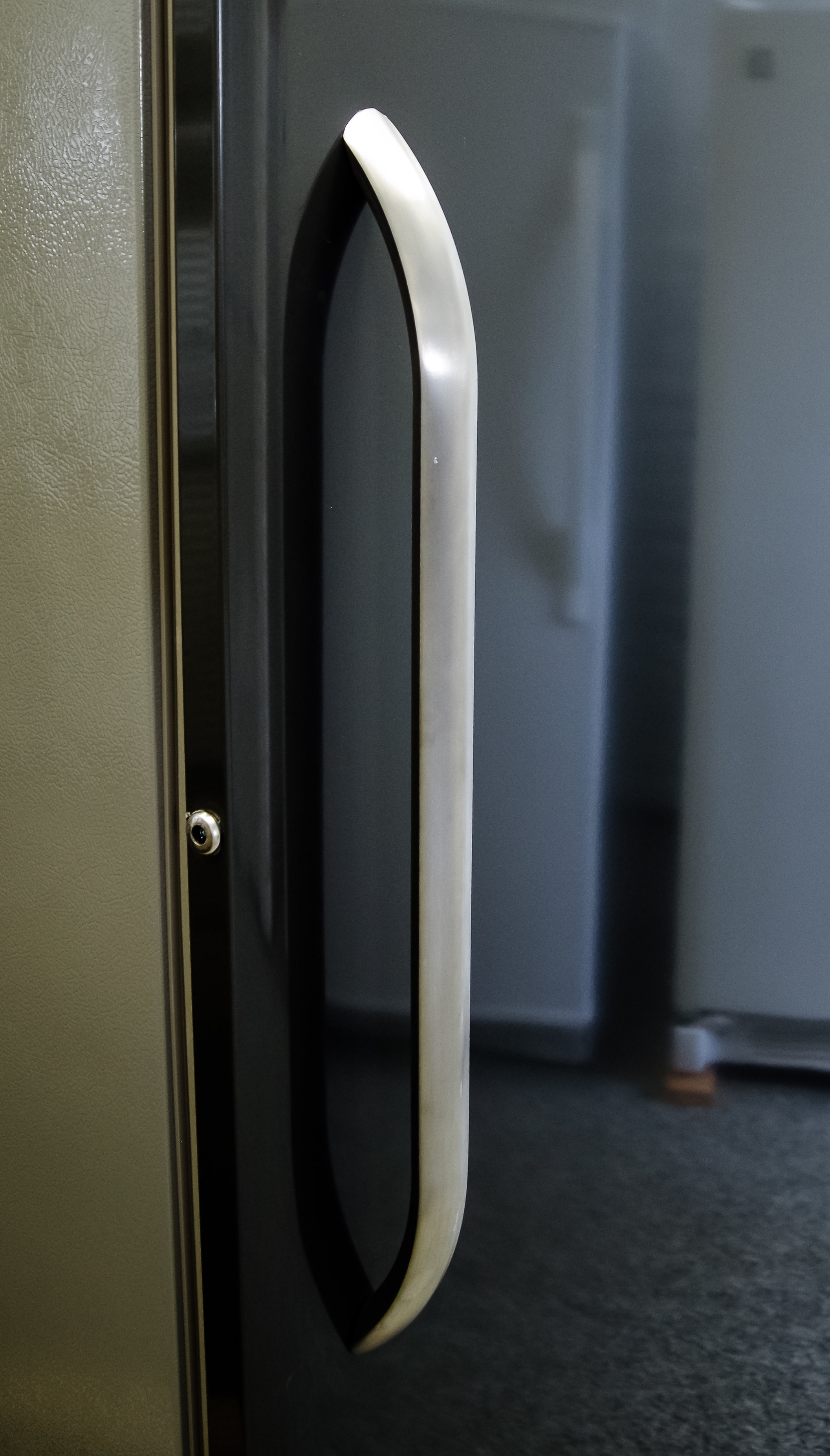 The chrome handle acts as an interesting visual contrast to the Frigidaire FFU27F2PT's slate door.