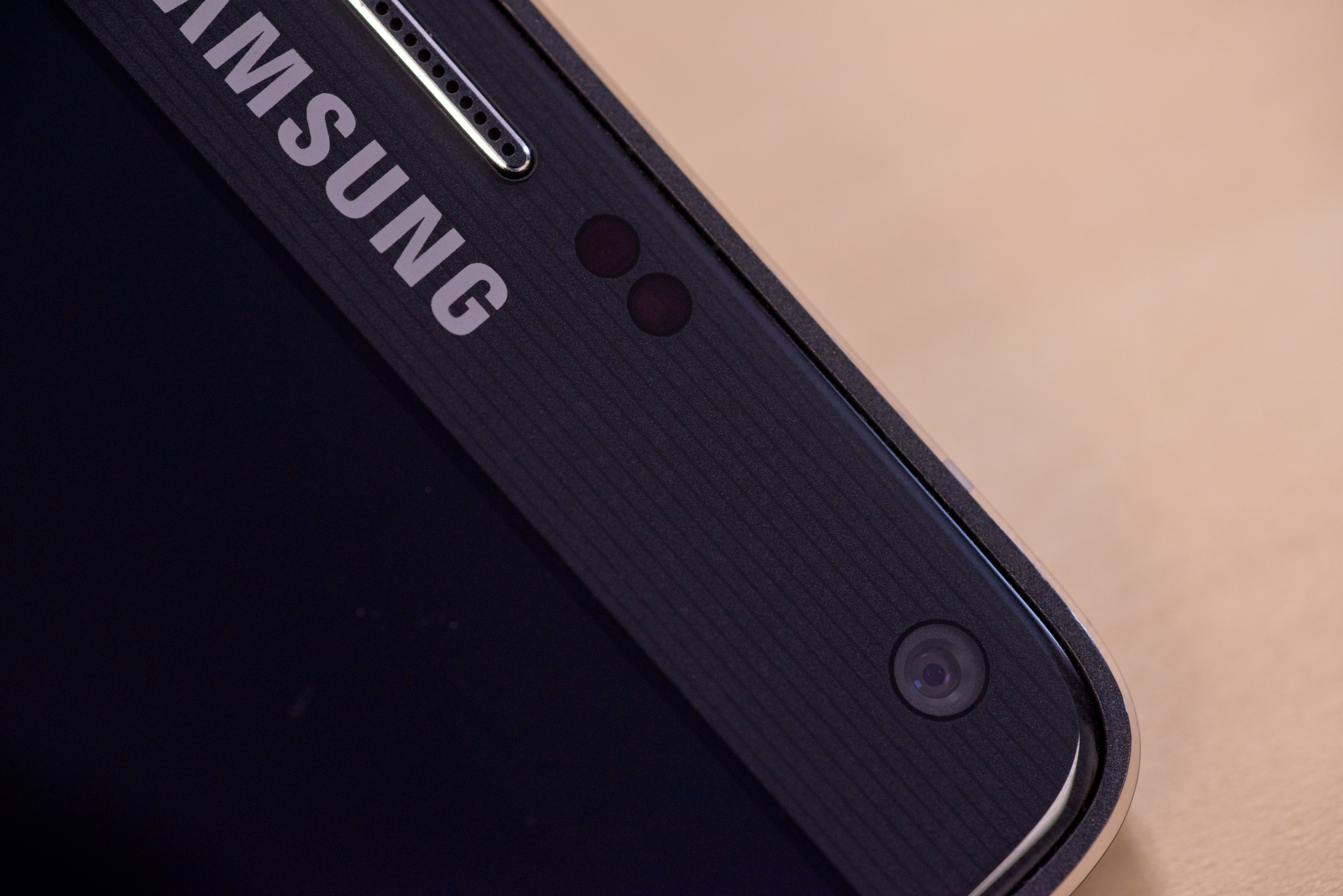 A photograph of the Samsung Galaxy Note 4's earpiece and user-facing camera.
