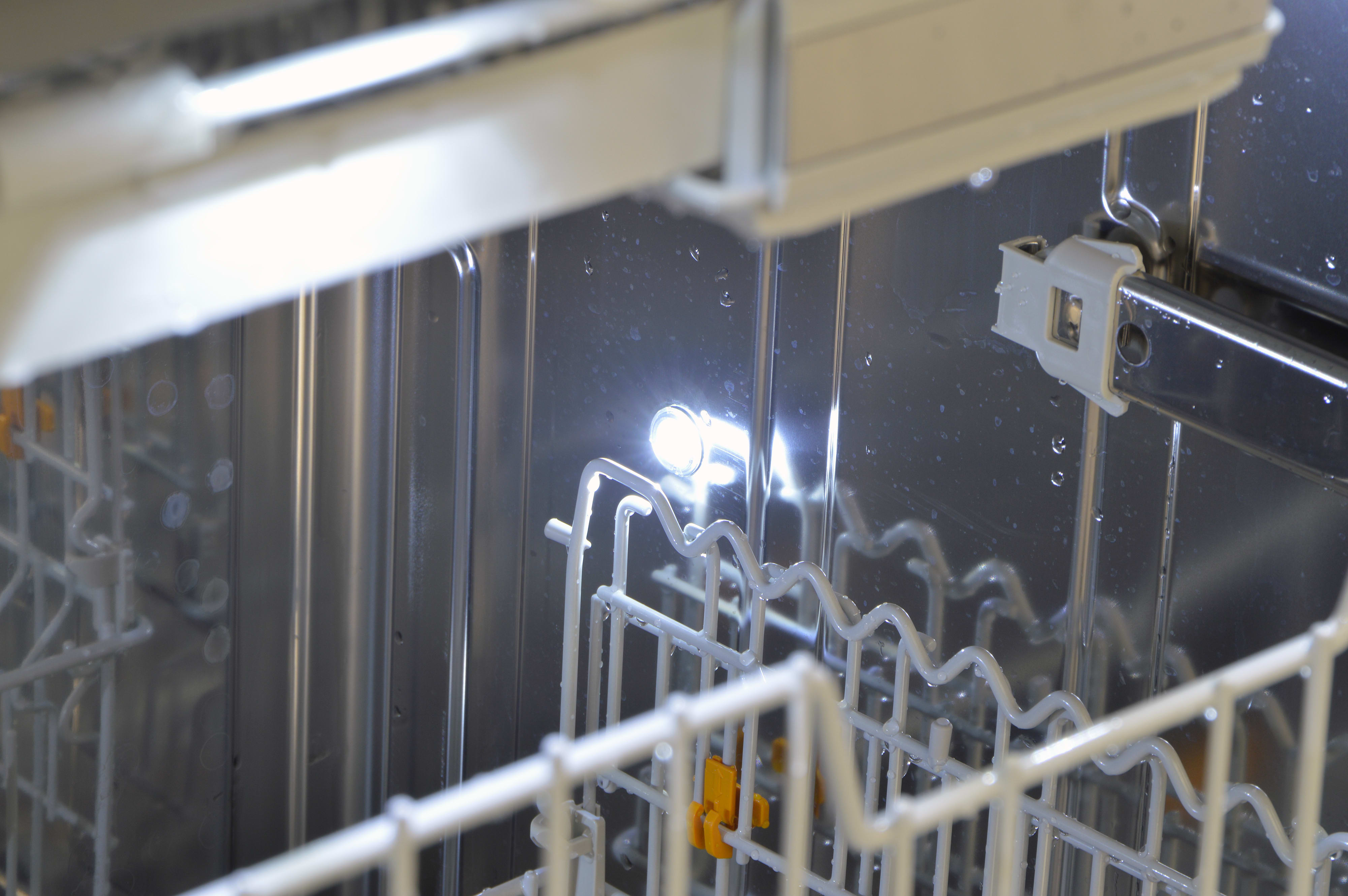 Closeup of an internal light deep inside the dishwasher's tub
