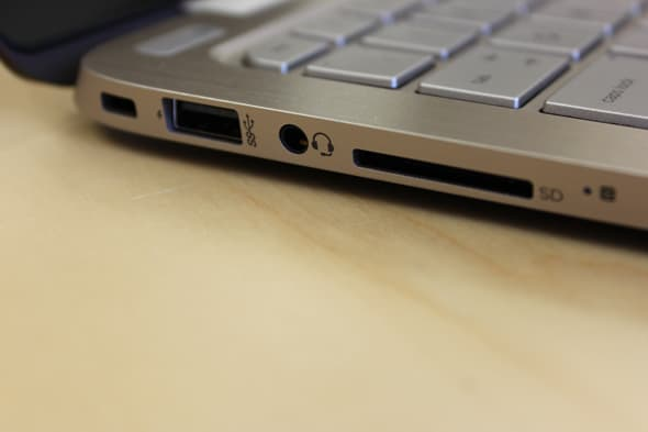 The Spectre's left side contains a security slot, a USB 3.0 port, a headphone jack, and an SD card reader.