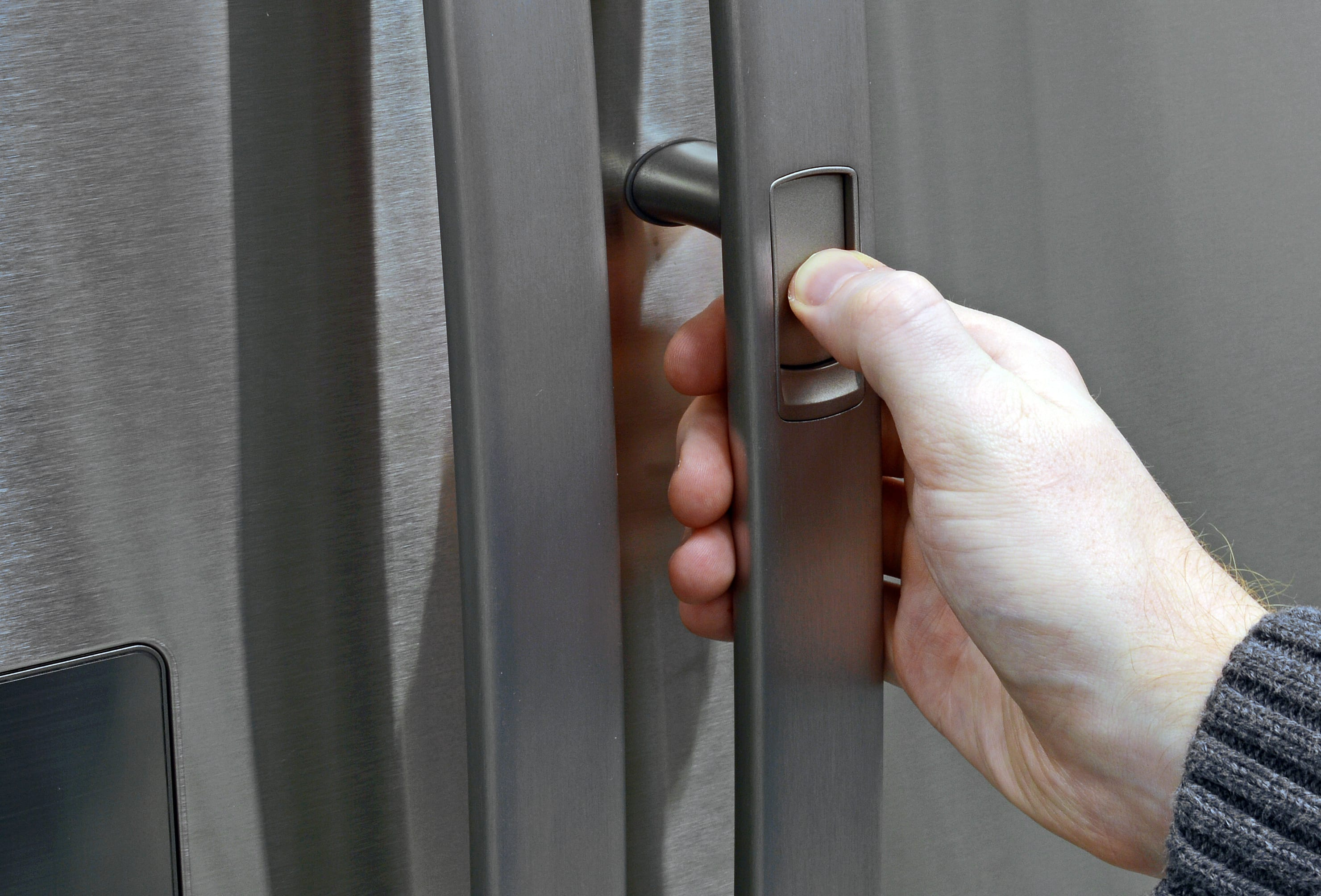 Access the Kenmore 70333's door-in-door storage from the outside by pressing a button found on the right door handle.